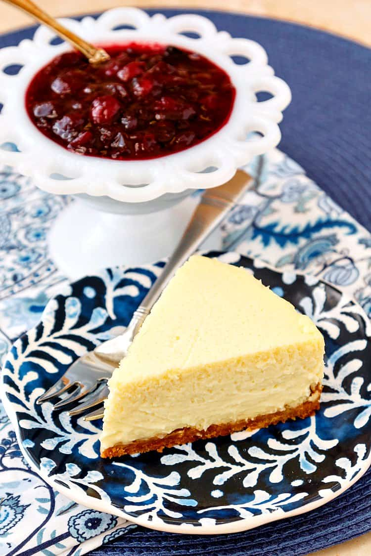 A slice of roasted corn cheesecake on a blue patterned plate with a white bowl of cranberry blueberry compote.