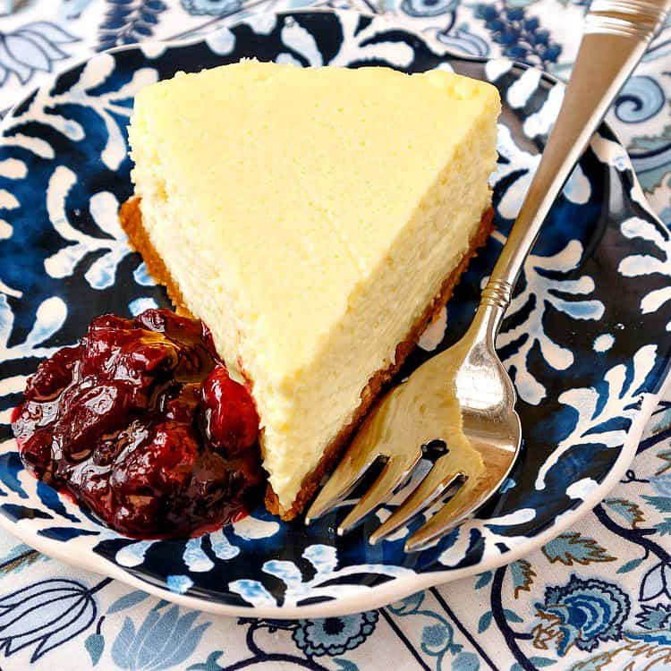 Roasted corn cheesecake slice on a blue and white plate with a fork and fruit compote.
