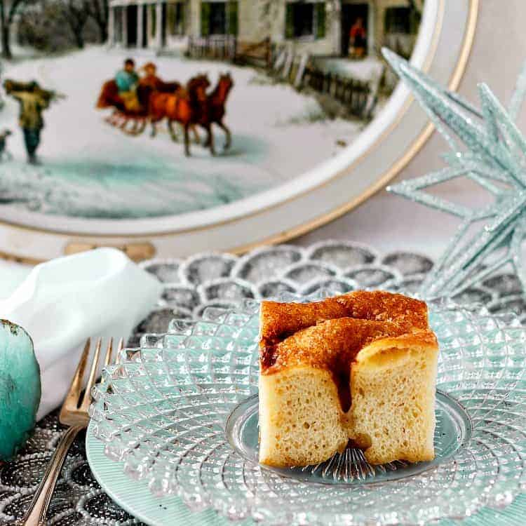 A slice of Moravian sugar cake on a glass plate on a table with winter holiday decorations.