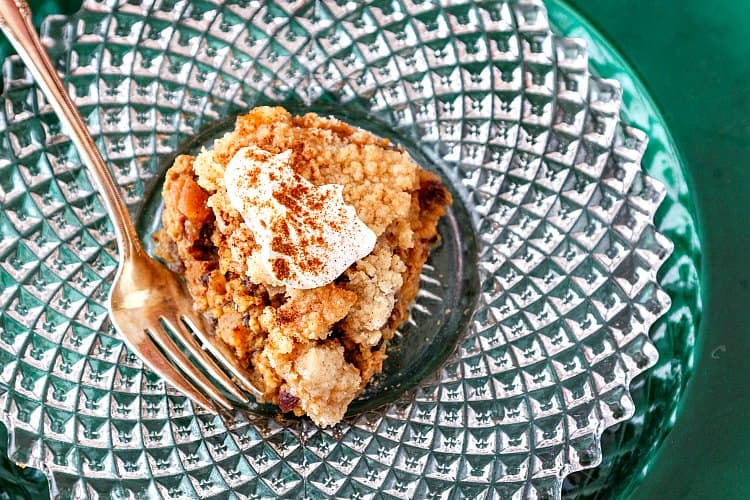 overhead shot of streusel topped breakfast or brunch baked oatmeal with whipped cream on a glass plate