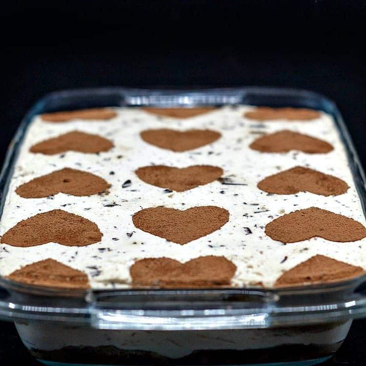 A casserole dish of tiramisu with cocoa powder hearts stenciled on top.