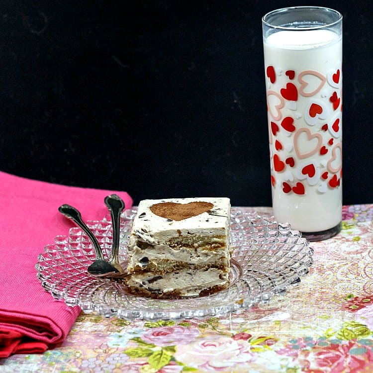 A slice of tiramisu with a chocolate cocoa powder heart stenciled on top. It sits on a glass plate with two forks and is served with a glass of milk.