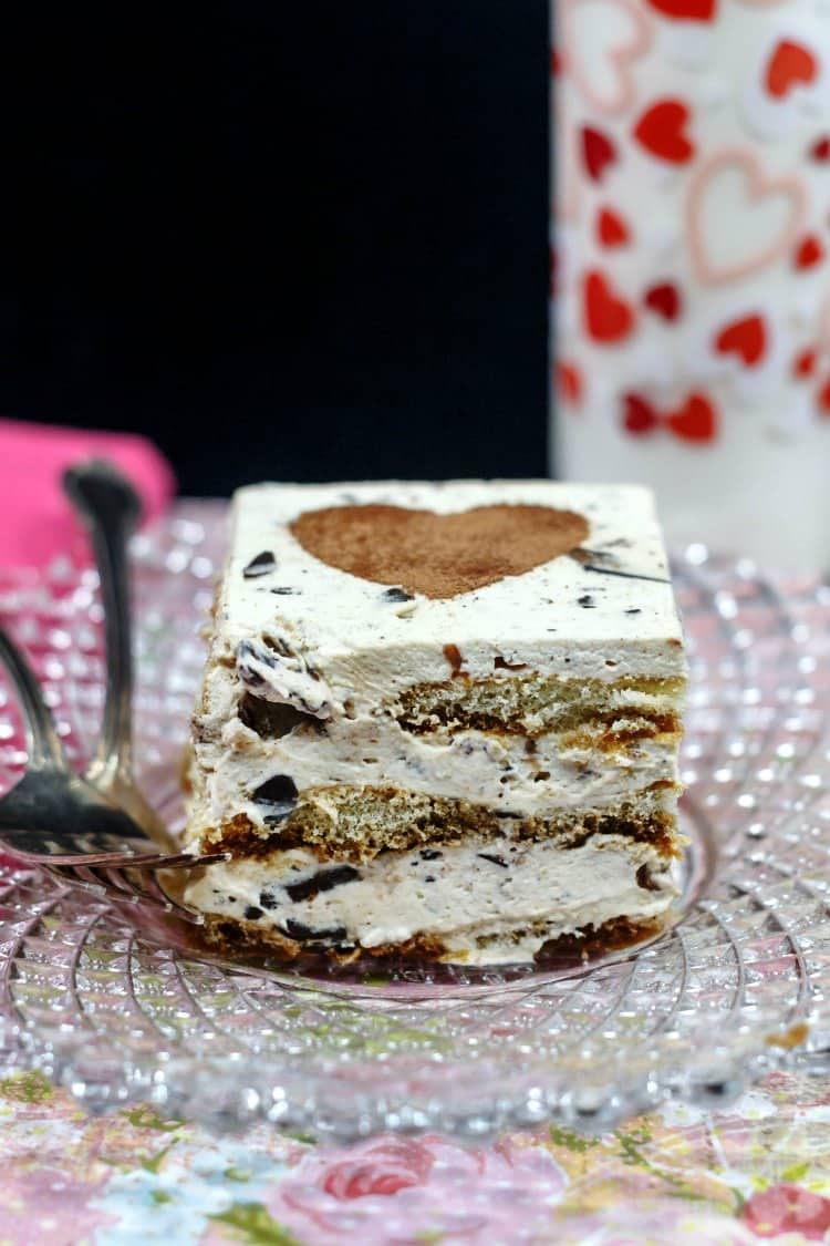 A slice of eggless tiramisu on a glass plate with a glass of milk in the background.