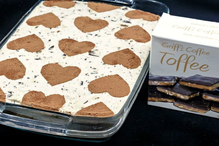 A 13x9 glass casserole dish full of eggless tiramisu decorated with stenciled cocoa powder hearts next to a box of toffee.