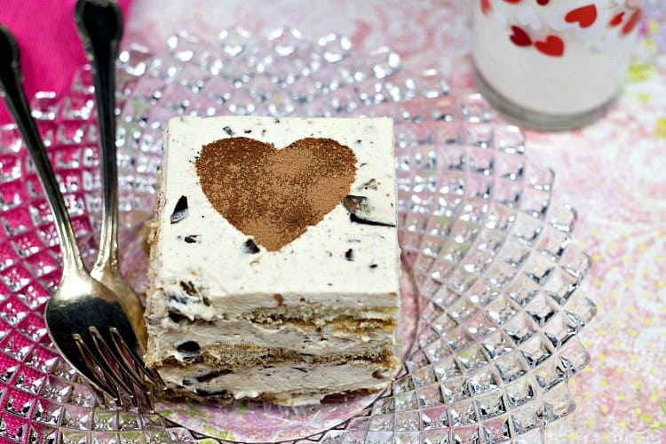 An overhead shot of a square slice of tiramisu with toffee bits in it and a stenciled cocoa powder heart on top.