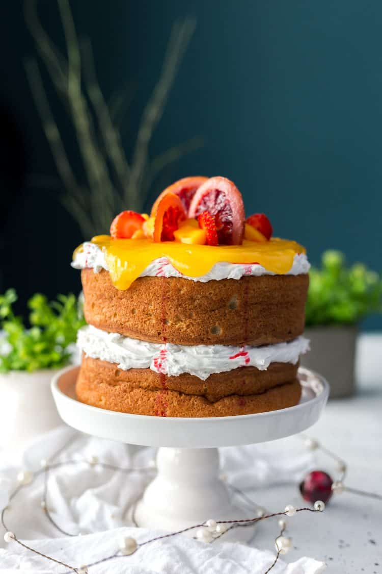 two layer sponge cake on white cake pedestal with whipped cream as filling and topping and decorated with orange slices and orange curd