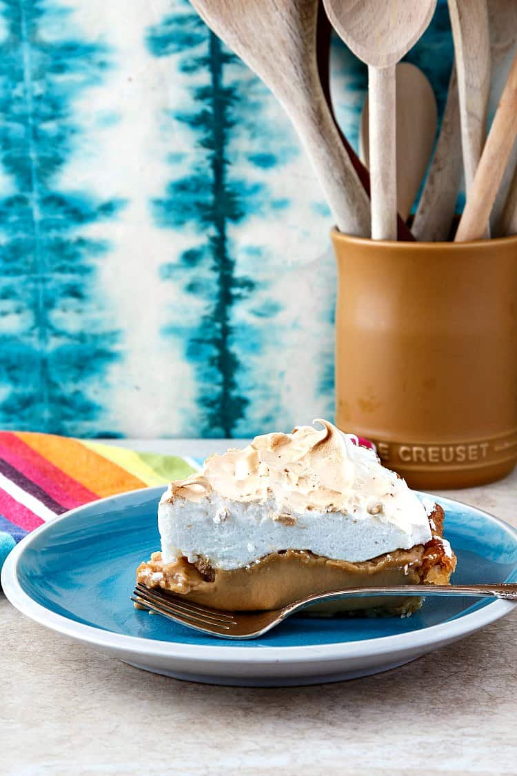 A slice of meringue-topped butterscotch pie on a blue plate.