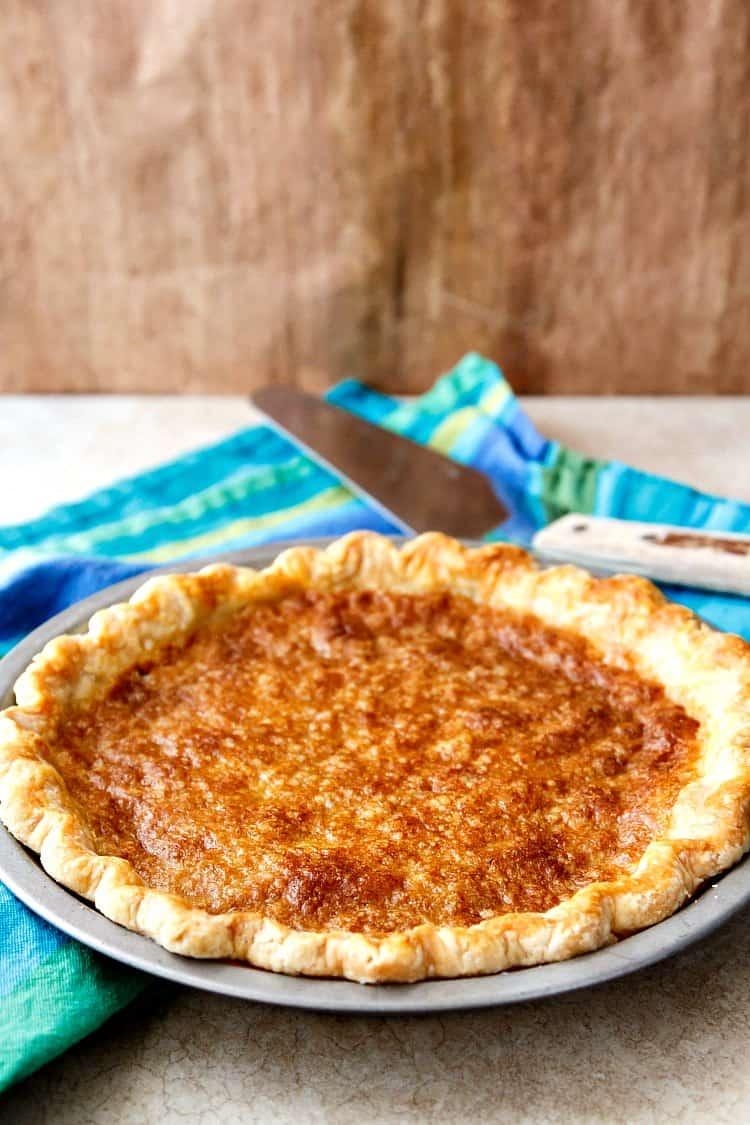 A whole golden vinegar pie in metal pie pan.