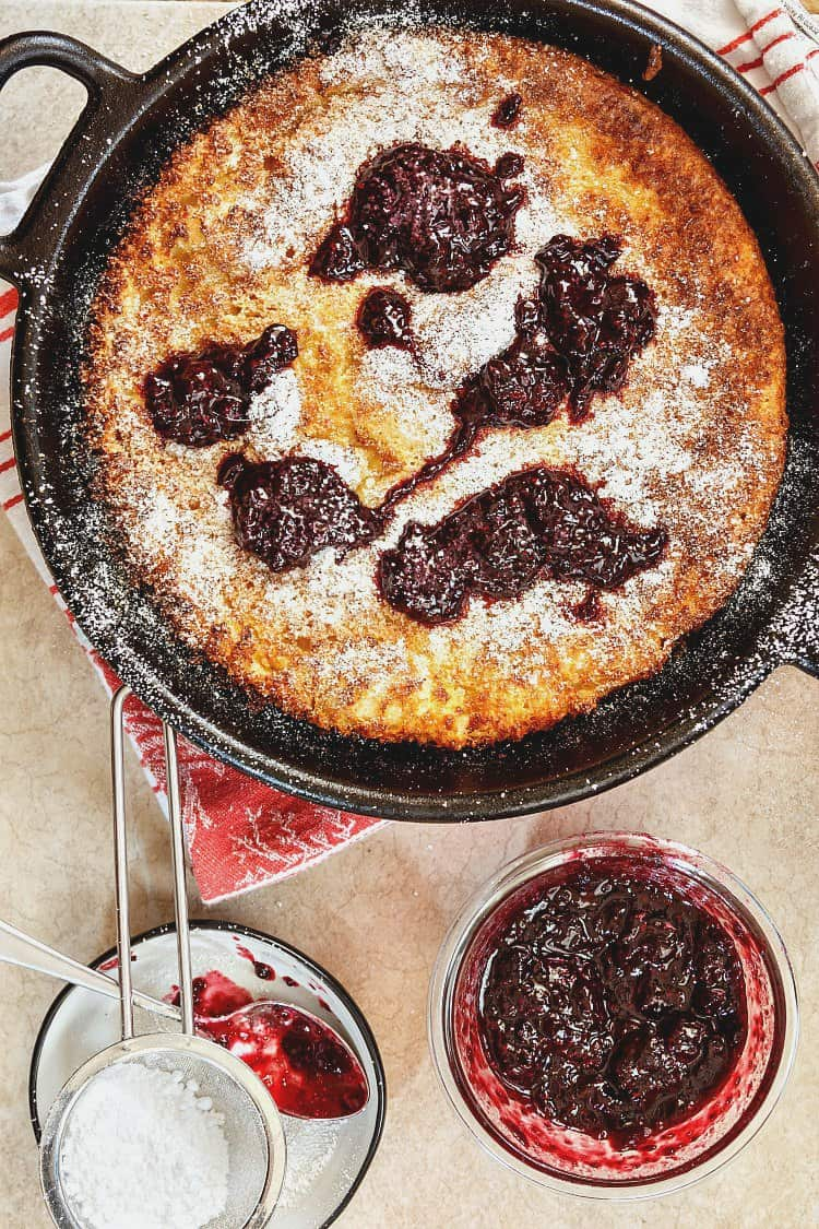 German pancakes baked in a cast iron frying pan topped with preserves and powdered sugar.