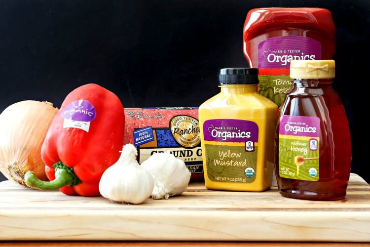 a cutting board with an array of organic products on it including mustard, honey, ketchup and sweet peppers