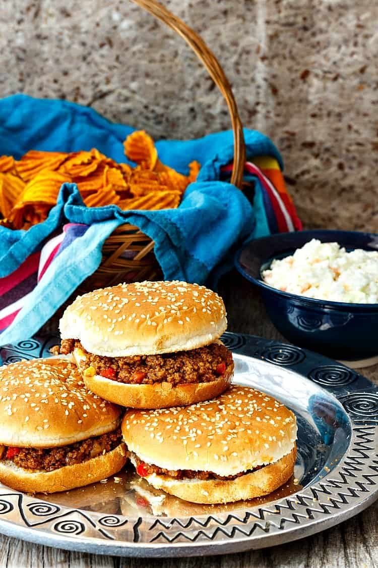 sloppy joes piled on a plate with a basket of chips and a bowl of coleslaw in the background