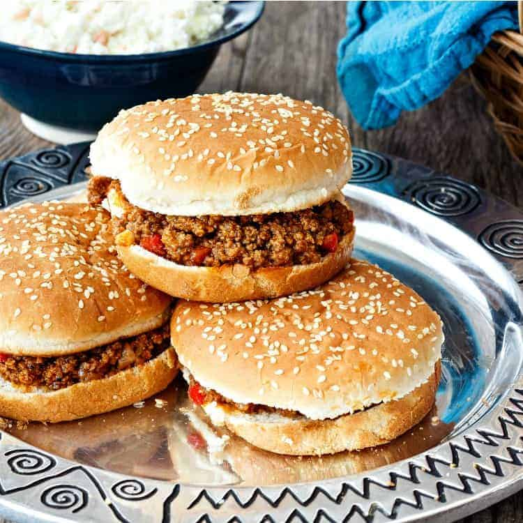 4 ground beef sandwiches on sesame buns piled on a pewter plate
