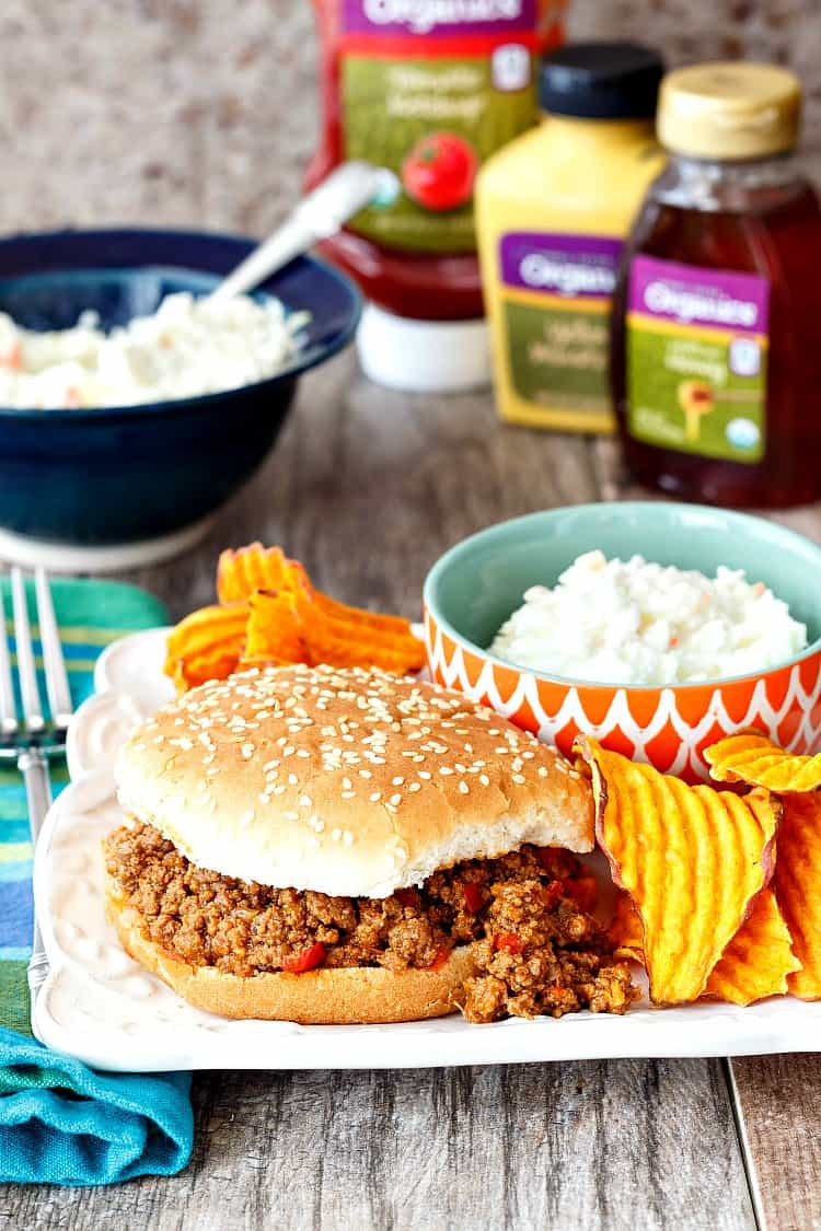 a sloppy joe on a sesame seed bun with coleslaw and ruffled chips as side dishes.