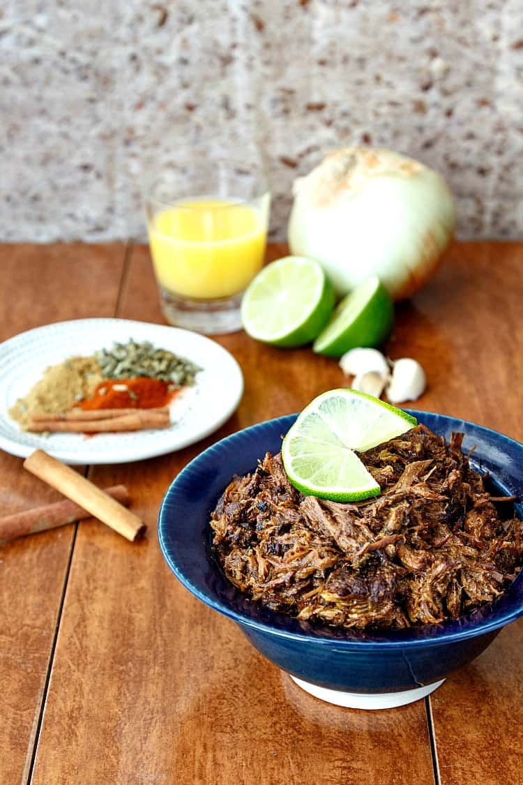 Shredded beef carnitas in a blue bowl, a plate of spices, and orange juice, cut lime, and an onion in the background.