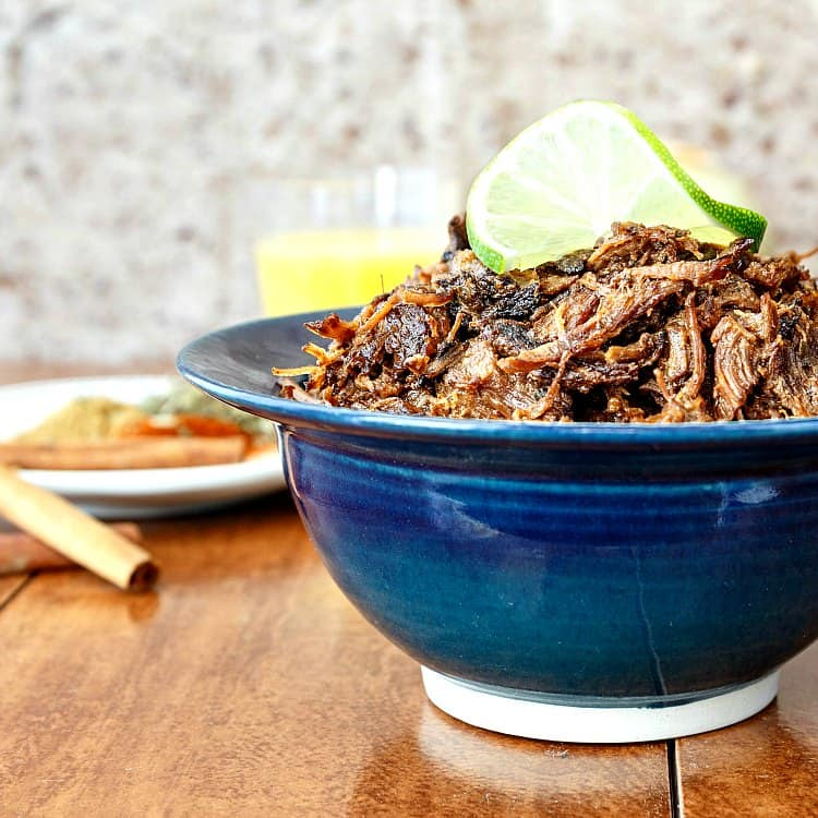 Beef carnitas made in an instant pot and piled into a blue bowl with a lime garnish.