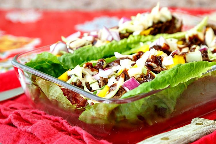Beef carnitas lettuce wraps in a rectangular glass dish on red cloth.