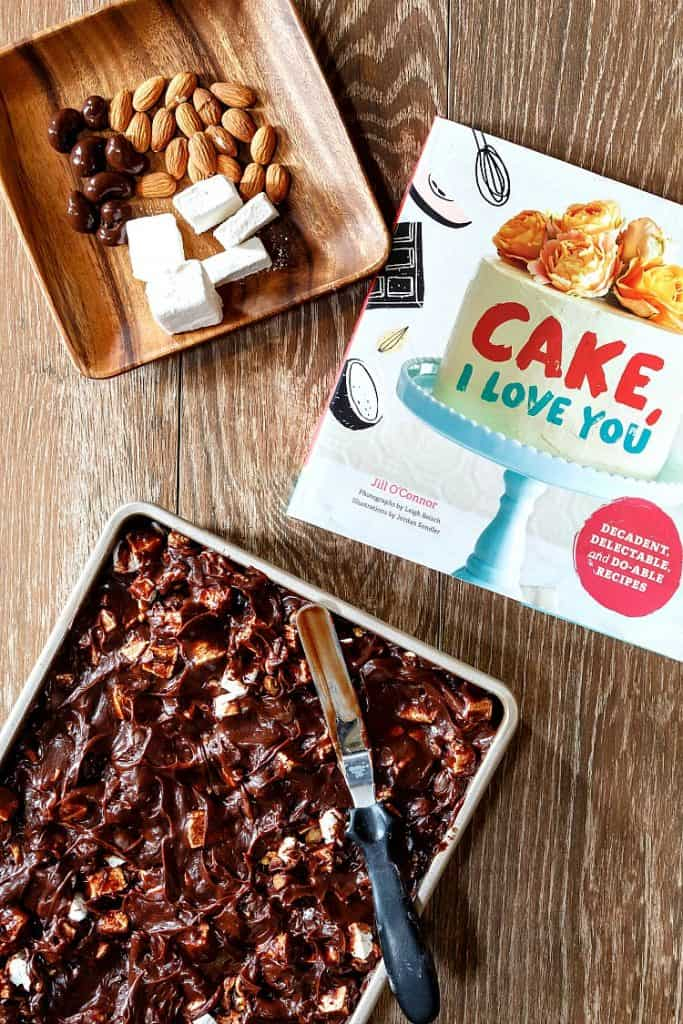 """Overhead shot of chocolate sheet cake with rocky road frosting, the cookbook """"Cake, I Love you"""", and a square wooden plate with chocolate covered cashews, toasted almonds, and homemade marshmallows."""