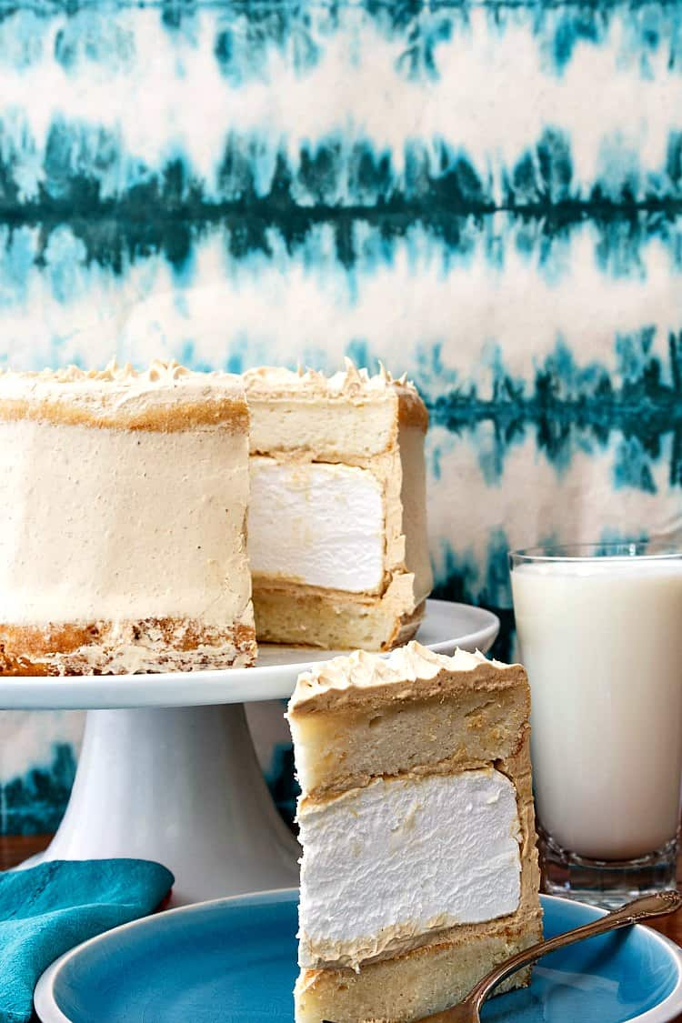 Layer cake with white cake layers, homemade marshmallow, and peanut butter buttercream on a blue plate. One slice is removed showing interior of cake. The slice is on a plate next to a glass of milk.
