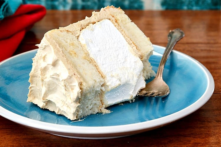 A slice of white cake layered with marshmallow and peanut butter Swiss meringue buttercream on a plate with a bite taken out of one corner.