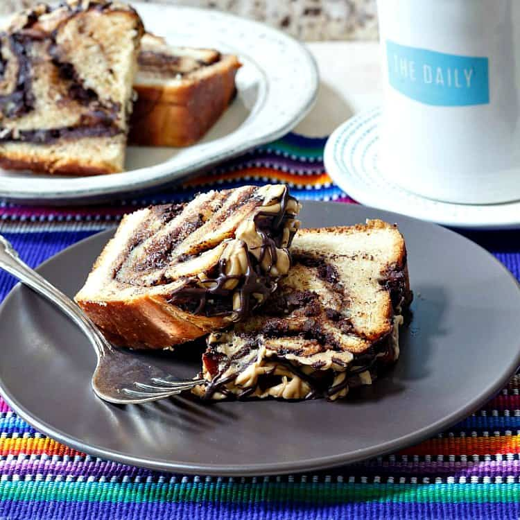 Two slices of chocolate babka on a brown plate with a fork on it with another plate of babka in the background and a coffee cup.