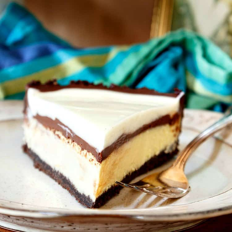 Close up shot of a slice of cheesecake pie with fudge sauce, head on, on a plate with a blue striped napkin in the background.