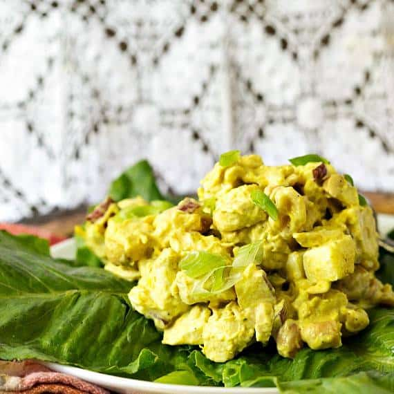 A scoop of curried chicken salad on a lettuce-lined plate.