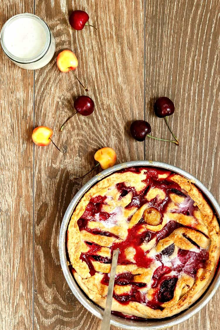 overhead shot of a round tin of deep dish cobbler or sonker with some whole cherries scattered around on a wooden background