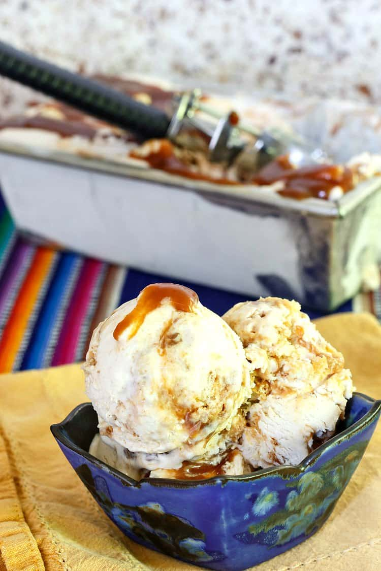A blue bowl of ice cream with caramel swirls and bits of cinnamon roll with the container of ice cream in the background.