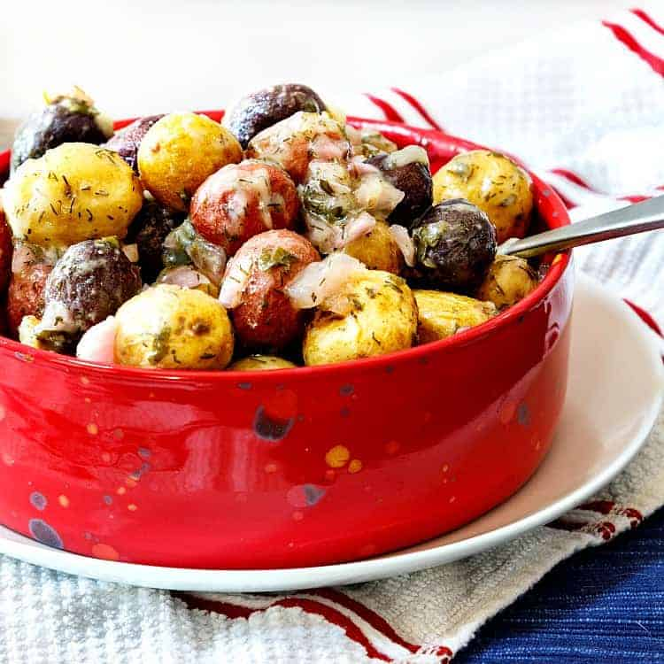 A red bowl of potato salad made with red, white and blue baby potatoes on a white plate with a spoon in it, ready for serving.