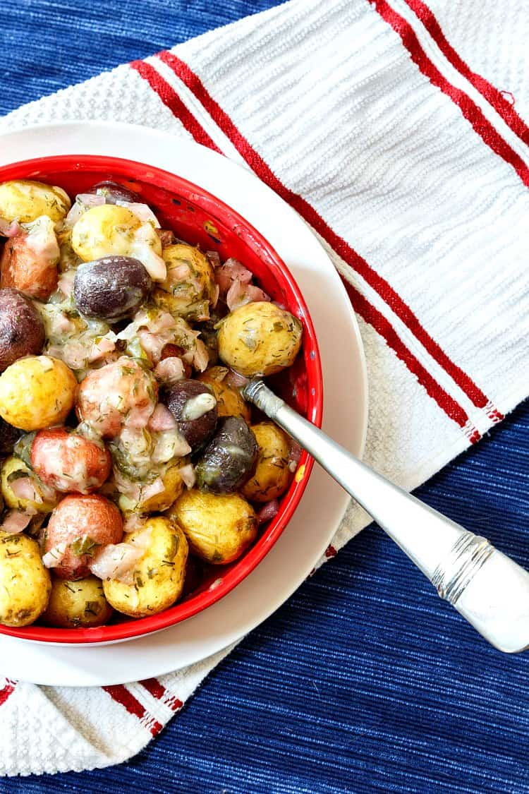 My no mayo potato salad made with whole baby red, white, and blue potatoes in a red bowl on a white plate with a blue placemat as the background.