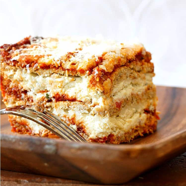 A slice of lasagna made with cauliflower pasta noodles on a wooden plate.
