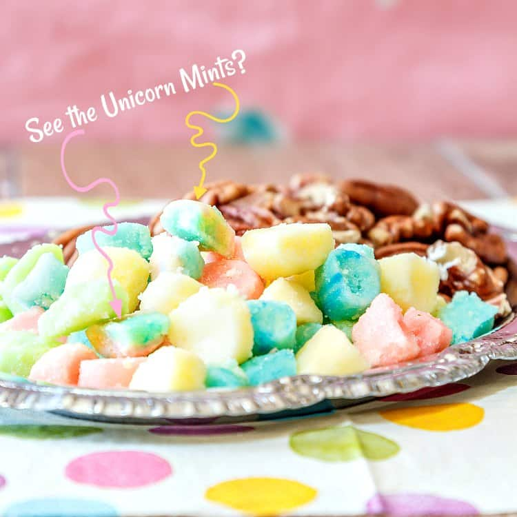 """A silver tray of mints and nuts with squiggly arrows pointing to two Unicorn mints. Text reads """"See the Unicorn Mints?""""."""