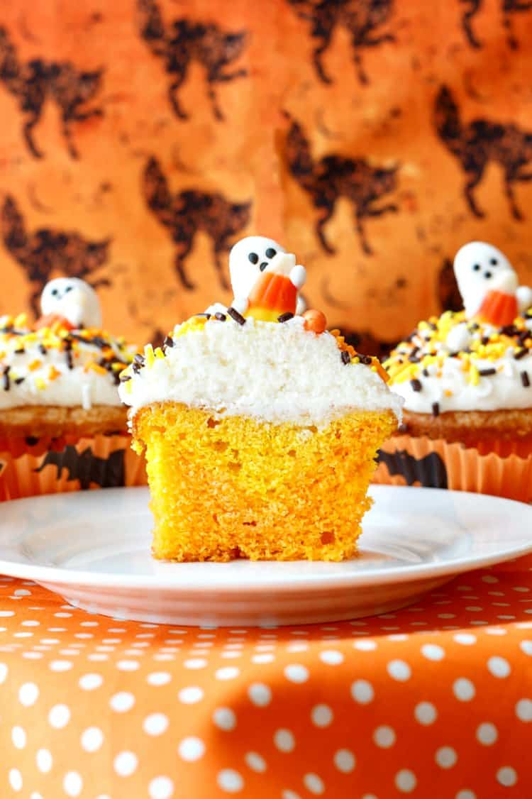 A cross section of a candy corn cupcake showing interior of cake colors.