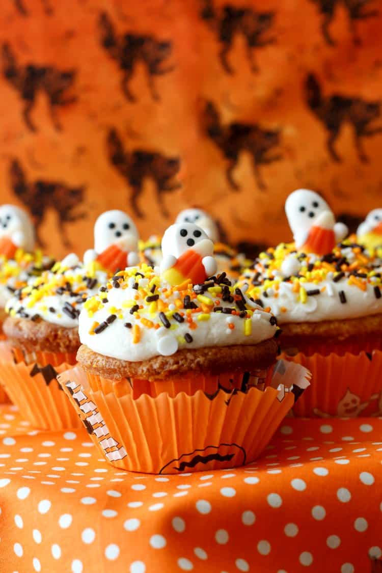 Candy corn cupcakes with ghost toppers on an orange background.