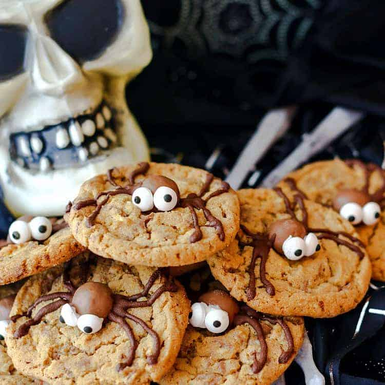 A pile if malted milk ball spider cookies on a plate with a plastic skull in the background.
