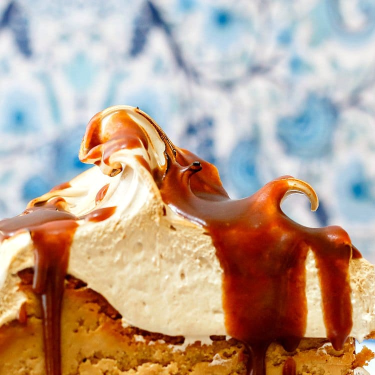 Thick brown sugar meringue on top of a  slice of gluten-free cheesecake with butterscotch sauce.