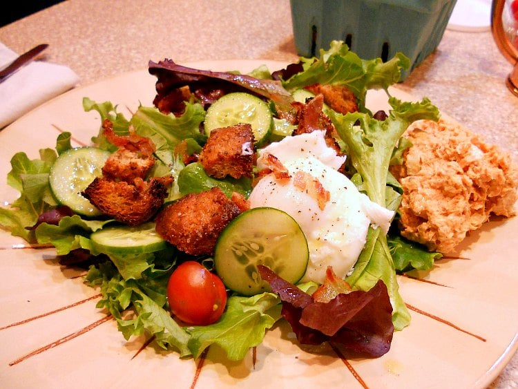 Plate of salad with lettuce, cucumbers, crumbled bacon, poached egg, and croutons.