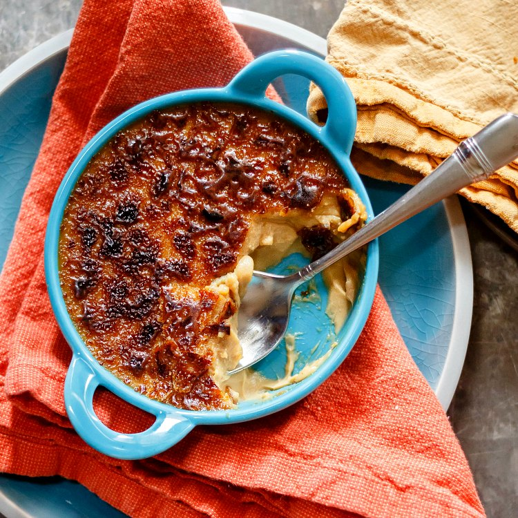 overhead shot of butterscotch creme brulee in a blue ramekin, partly eaten with a spoon in it