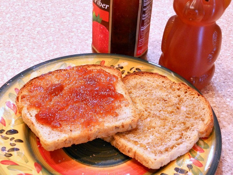 Two toasted pieces of bread, one with honey drizzled on it and one with jam, on a plate.