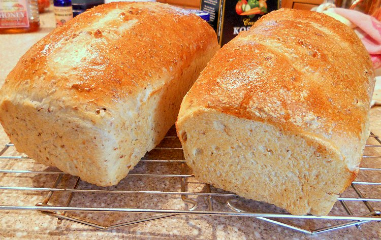 Two loaves of homemade bread cooling on a cooling rack.