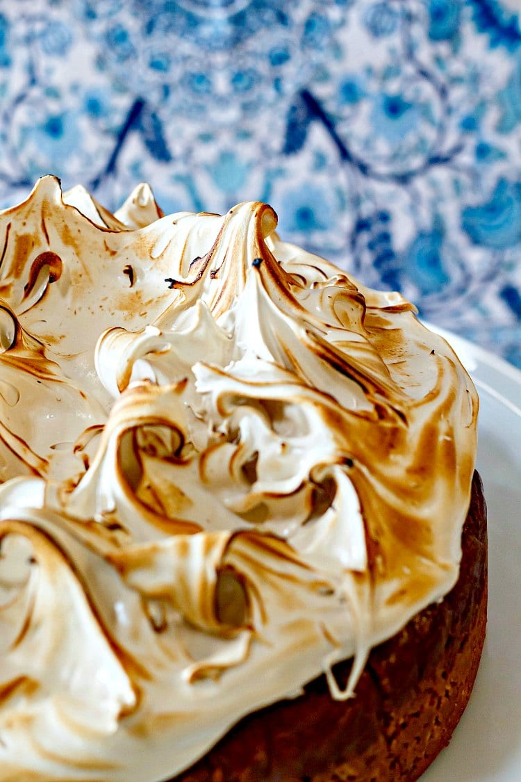 A whole gluten-free butterscotch cheesecake on a white cake stand with lots of browned meringue on top.