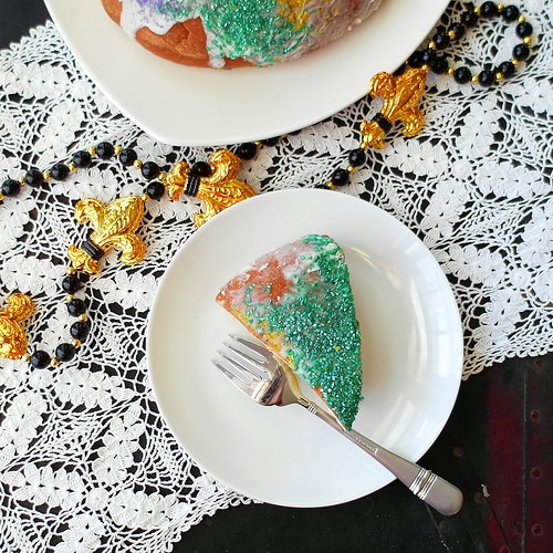 One serving of cinnamon king cake with green sprinkles on a white plate with a metal fork. Mardi gras beads of gold and black are on the crocheted table runner by the plate.