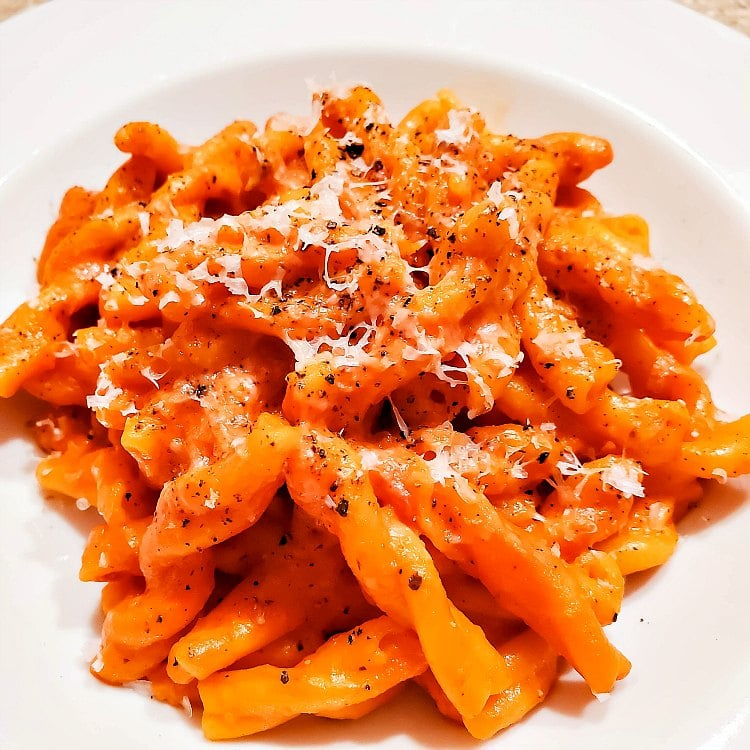 A plate of rotini pasta coated in sauce and topped with Parmesan cheese and black pepper.