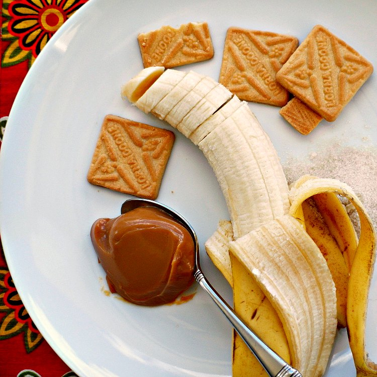sliced banana, spoonful of dulce de leche and square lorna doone cookies on a plate