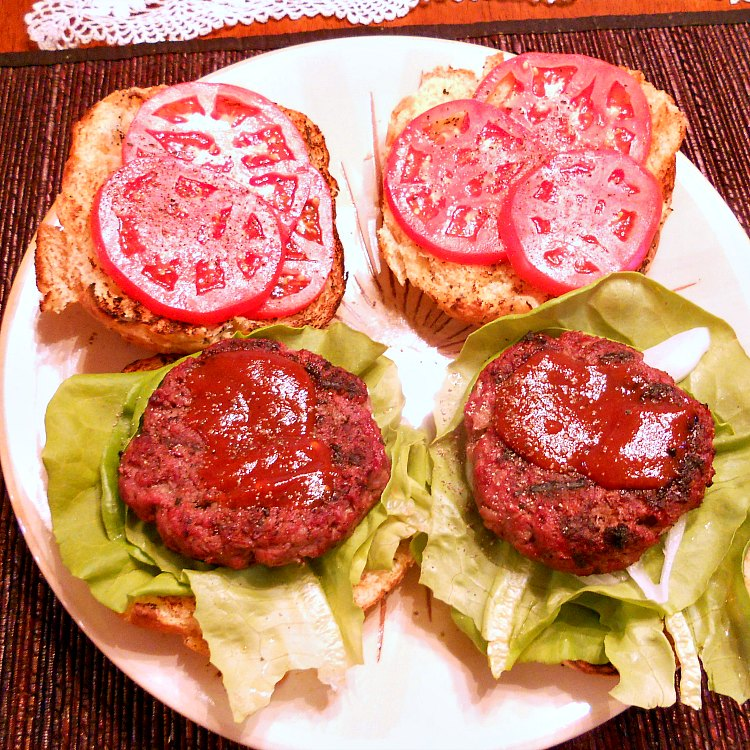2 bison burgers on lettuce with the buns open to show the sauce and sliced tomatoes.