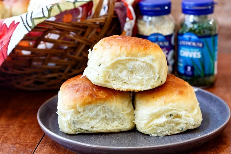 3 potato rolls on a plate with glass jars of freeze dried garlic and chives in the background.