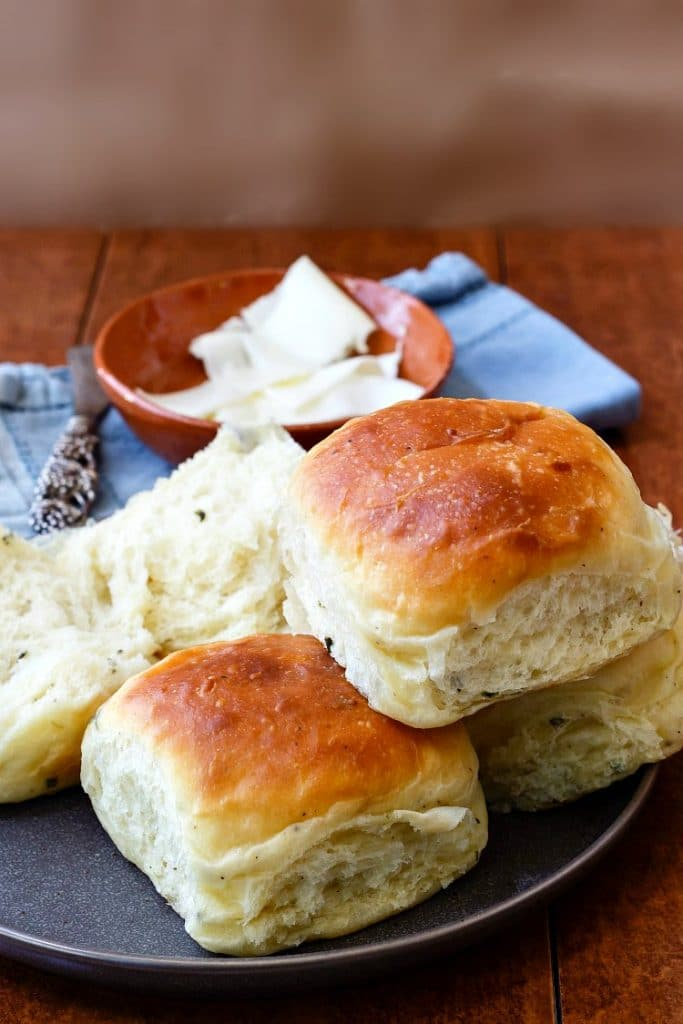 Thanksgiving dinner rolls on a plate, one is split open, with a bowl of butter in the background.