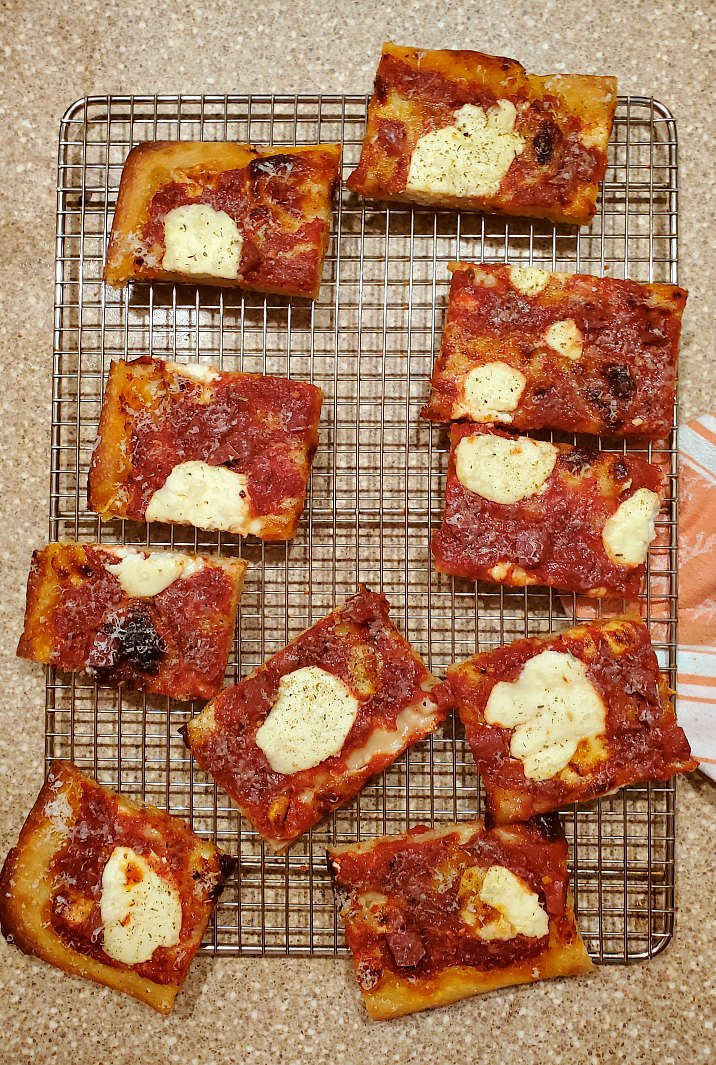 Grandma pizza dough recipe baked up with ricotta, mozzarella, fontina and parmesan cheese and cut into squares on a cooling rack.
