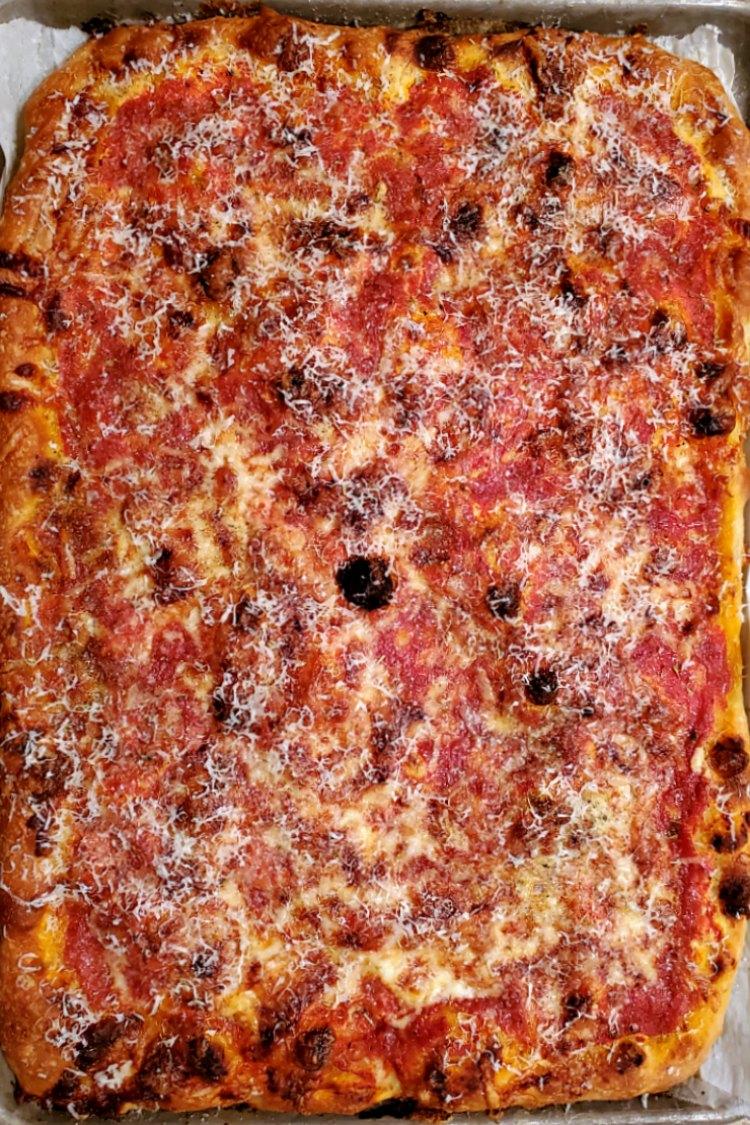 A rectangular baked lasagna pizza.