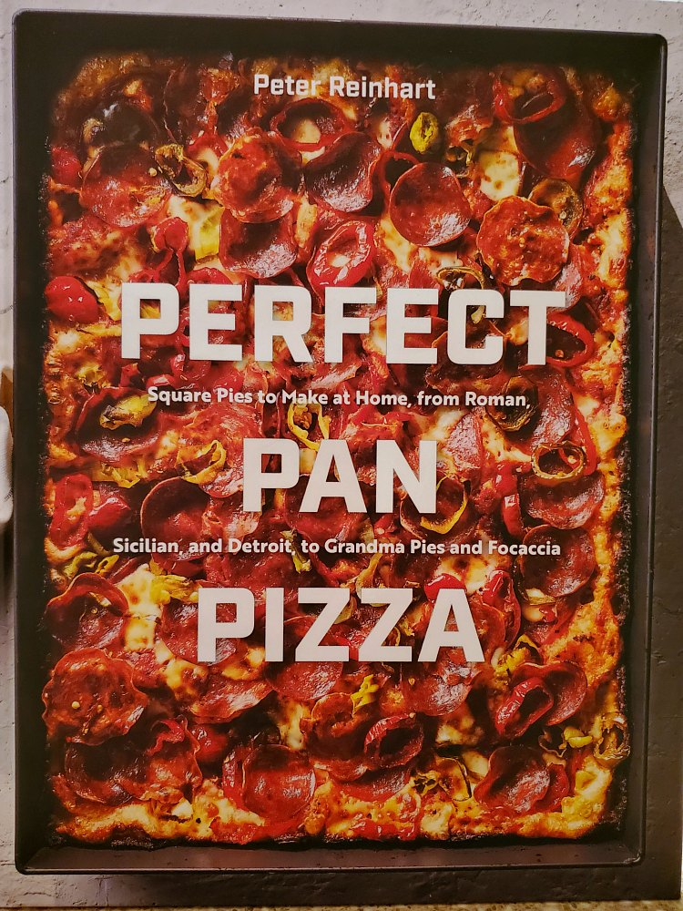 """Front of cookbook: """"Peter Reinhart, Perfect Pan Pizza, Square pies to make at home from Roman, Sicilian, and Detroit to Grandma pies and focaccia""""."""
